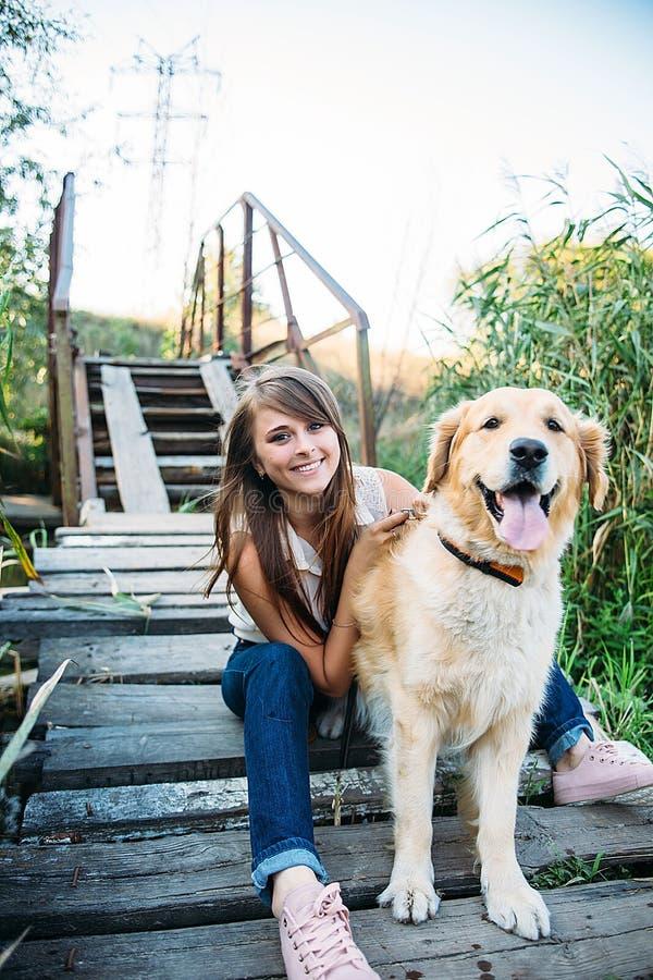 Ung härlig och le flicka som spelar med en hund royaltyfria bilder