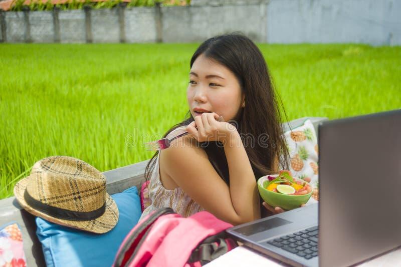 Ung härlig och lycklig asiatisk digital nomad eller turist- kvinnanätverkande för kines utomhus med att tycka om för bärbar dator arkivbild