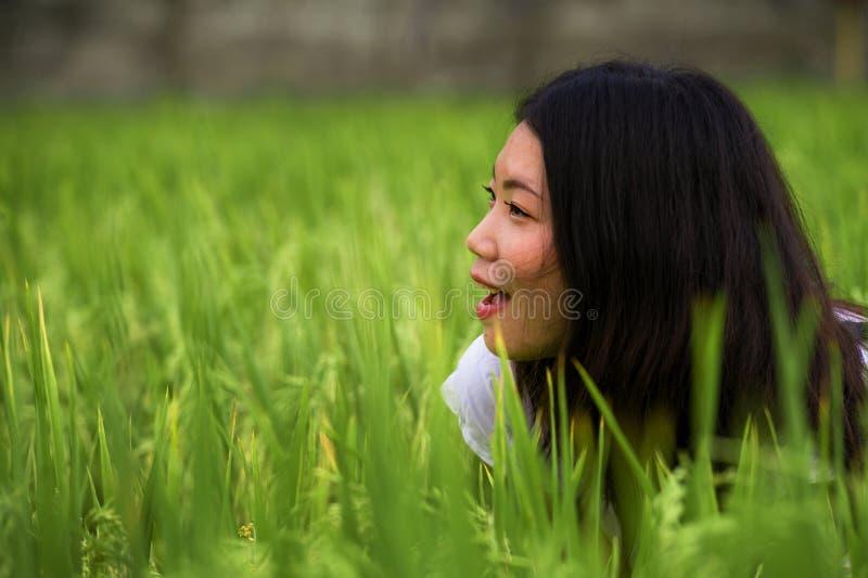 Ung härlig och lycklig asiatisk kinesisk turist- flicka som har rolig känsla som är fri på den tropiska risfältet som tycker om e arkivbild