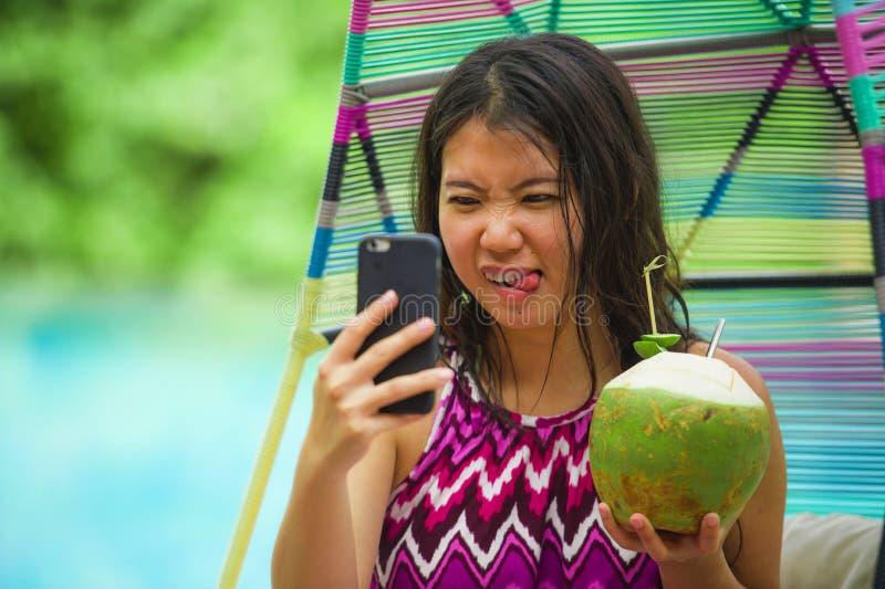 Ung härlig och lycklig asiatisk koreansk turist- kvinna som dricker kokosnötvatten som tar selfiebilden med mobiltelefonen på lyx arkivfoto