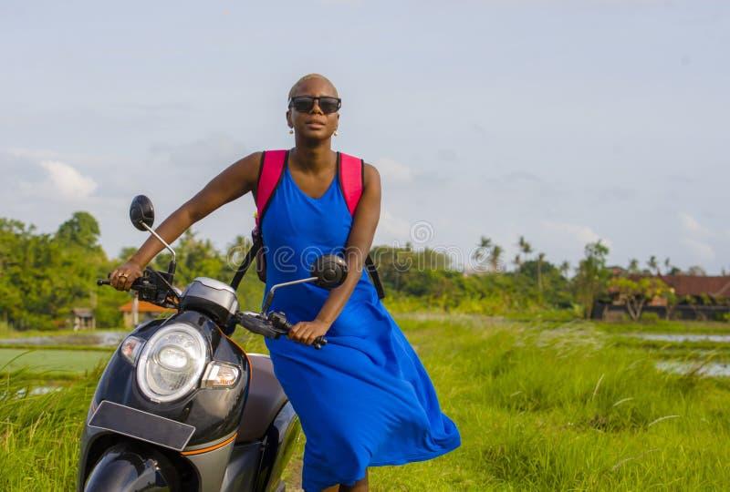 Ung härlig och lycklig turist- afrikansk amerikansvart kvinna som omkring ser med sparkcykelmopeden på tropiska länder för grönt  arkivfoton