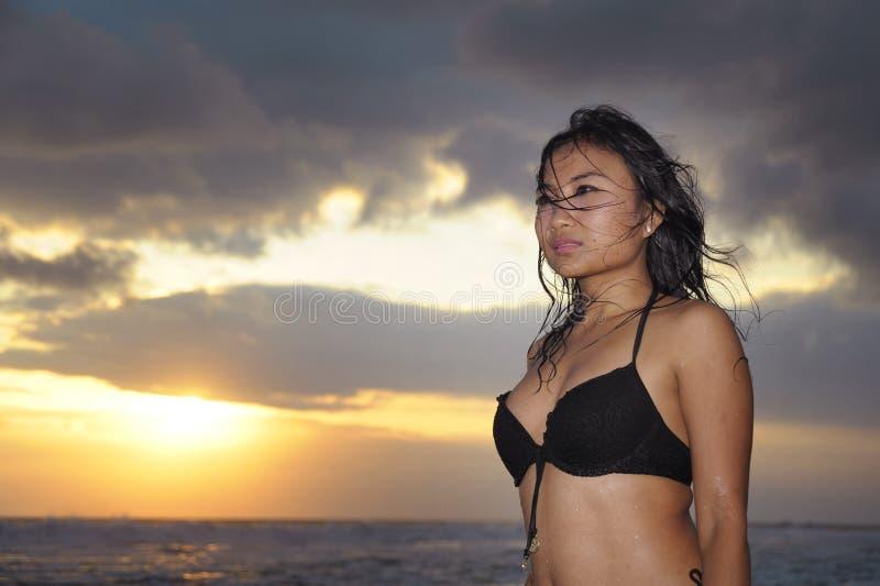 Ung härlig och sexig asiatisk kvinna i svart kopplat av posera för bikini ha gyckel på solnedgångstranden i den Bali ön av Indone royaltyfri fotografi