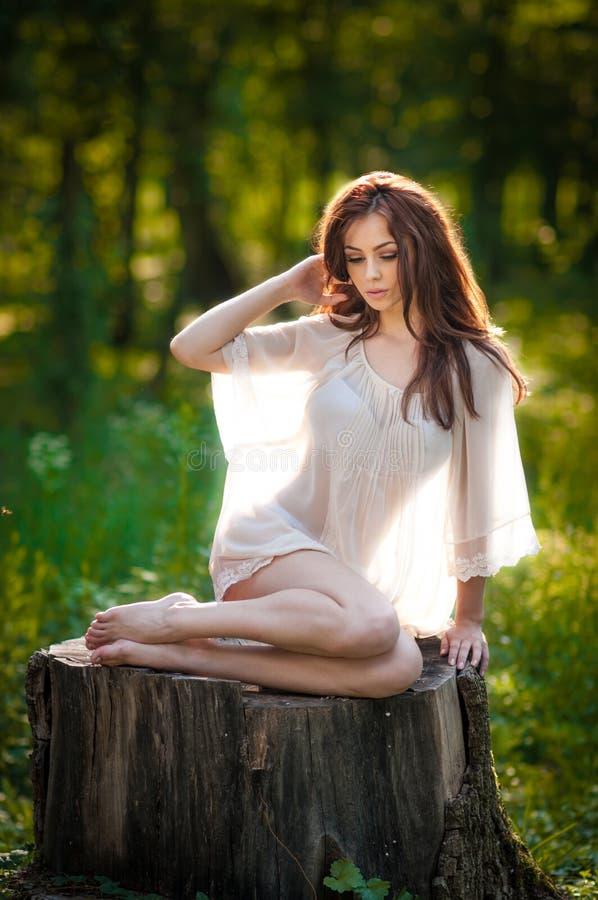 Ung härlig röd hårkvinna som bär en genomskinlig vit blus som poserar på en stubbe i en trendig sexig flicka för grön skog royaltyfria bilder