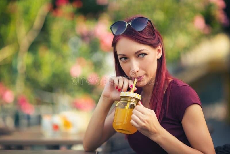 Ung härlig röd hårkvinna som dricker fruktsaft arkivfoto