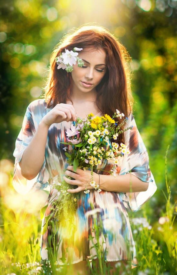 Ung härlig röd hårkvinna som rymmer en bukett för lösa blommor i en solig dag Stående av den attraktiva långa hårkvinnlign med bl royaltyfri fotografi