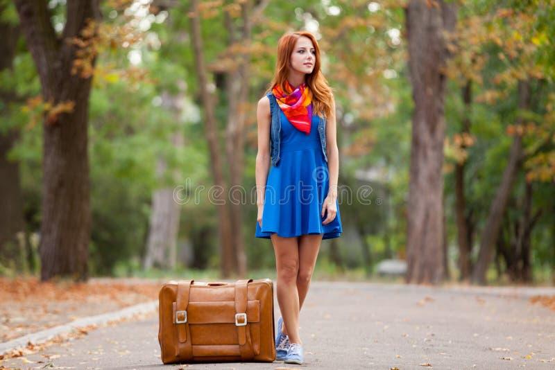 Ung härlig rödhårig mankvinna med resväskan royaltyfria bilder