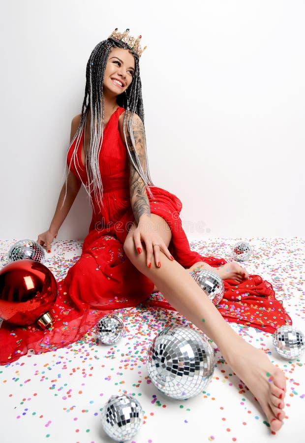 Ung härlig sexig kvinna i elegant rött klänningsammanträde i guld- krona med julgarneringbollen och konfettier royaltyfria bilder