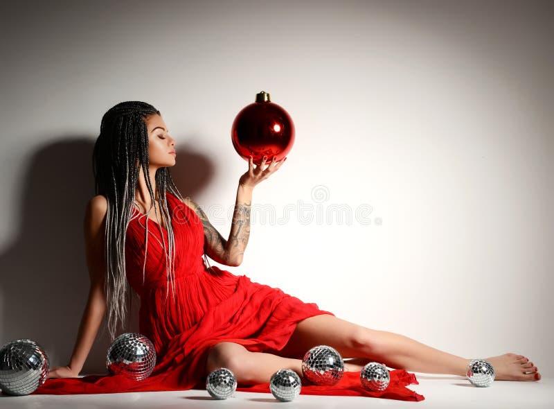 Ung härlig sexig kvinna i elegant rött klänningsammanträde i guld- krona med julgarneringbollen och konfettier fotografering för bildbyråer