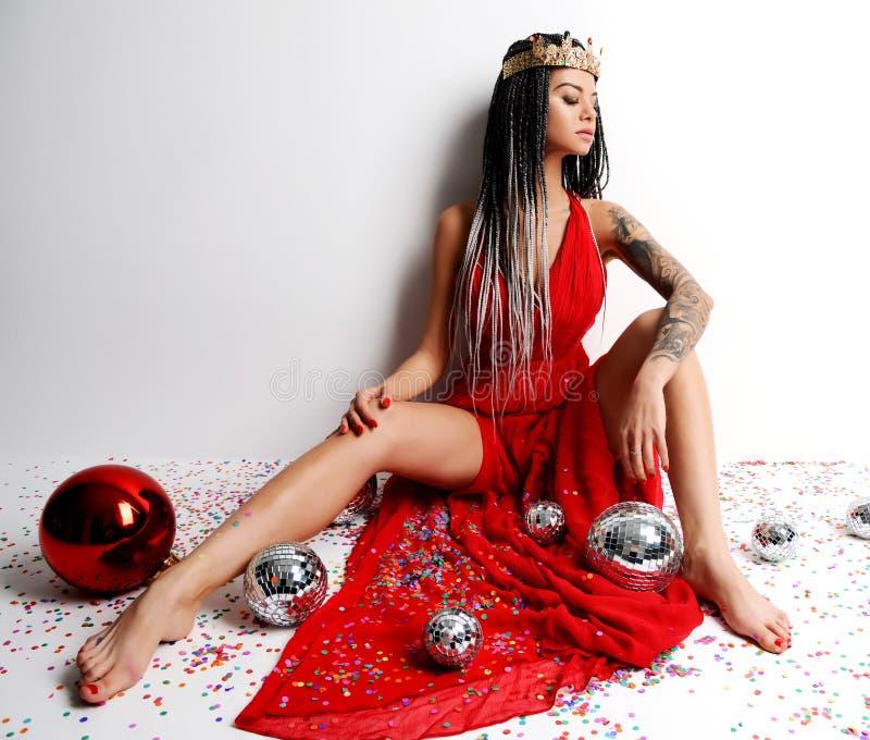 Ung härlig sexig kvinna i elegant rött klänningsammanträde i guld- krona med julgarneringbollen och konfettier royaltyfria foton