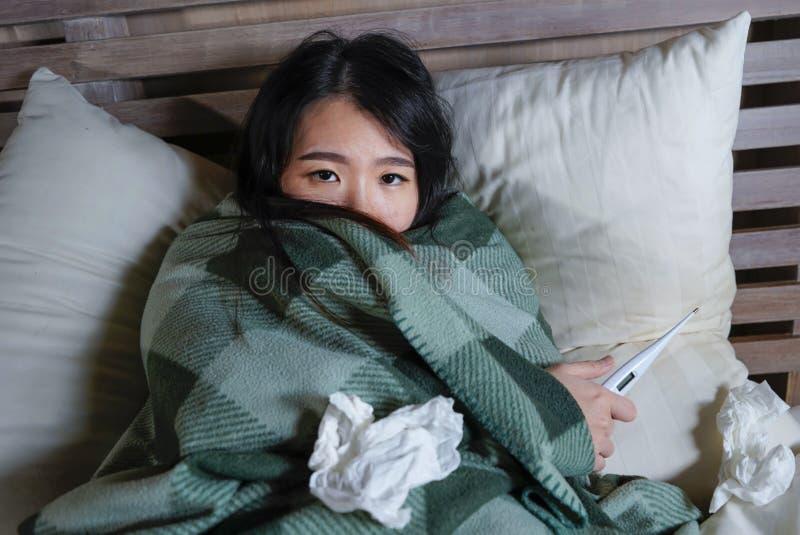 Ung härlig sjuk och utmattad asiatisk kinesisk kvinna som lider förkylning- och influensainnehavtermometern som har temperaturen  royaltyfri foto