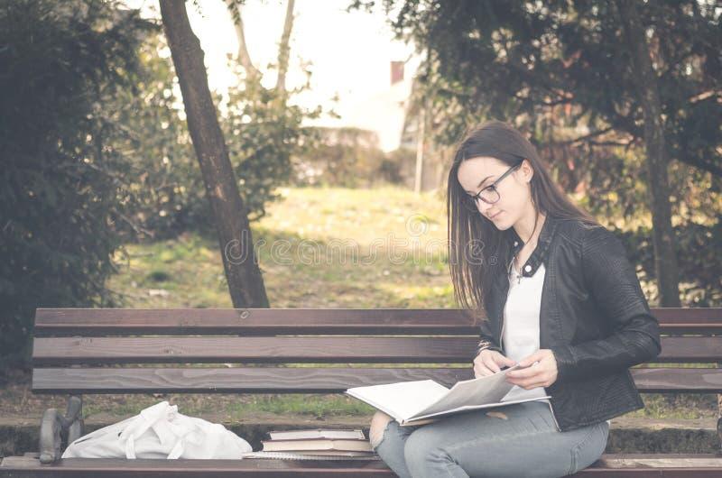 Ung härlig skola- eller högskolaflicka med ögonexponeringsglas som sitter på bänken i parkera som läser böckerna och studien för  royaltyfri fotografi