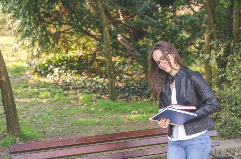 Ung härlig skola- eller högskolaflicka med exponeringsglas som sitter på bänken i parkera som läser böckerna och studien för exam arkivbilder