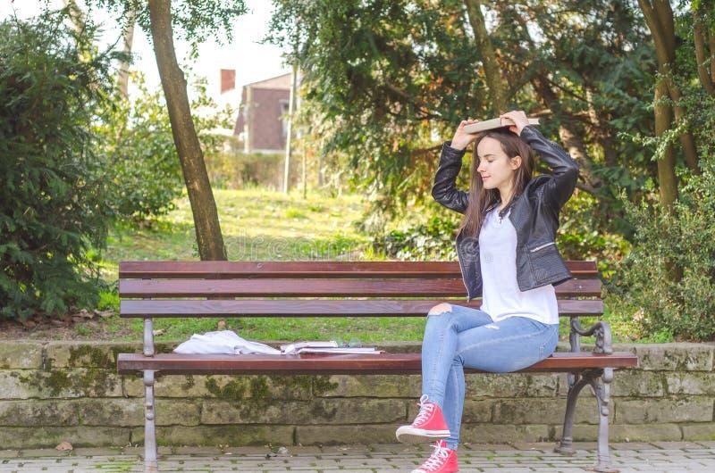 Ung härlig skola- eller högskolaflicka med exponeringsglas som sitter på bänken i parkera som läser böckerna och studien för exam royaltyfri foto