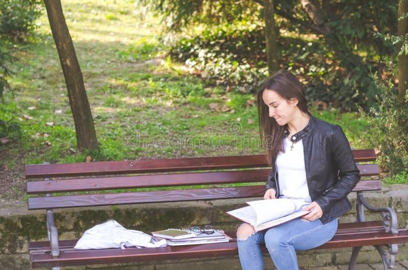 Ung härlig skola- eller högskolaflicka med exponeringsglas som sitter på bänken i parkera som läser böckerna och studien för exam royaltyfria bilder