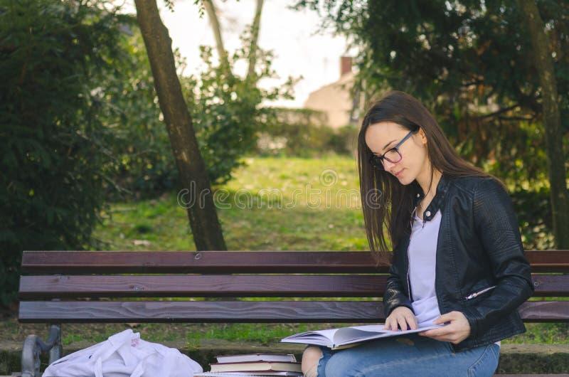 Ung härlig skola- eller högskolaflicka med exponeringsglas som sitter på bänken i parkera som läser böckerna och studien för exam royaltyfria foton