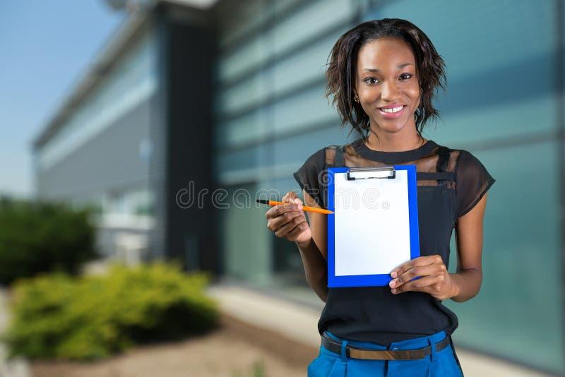 Ung härlig skrivplatta för afrikansk amerikankvinnavisning fotografering för bildbyråer