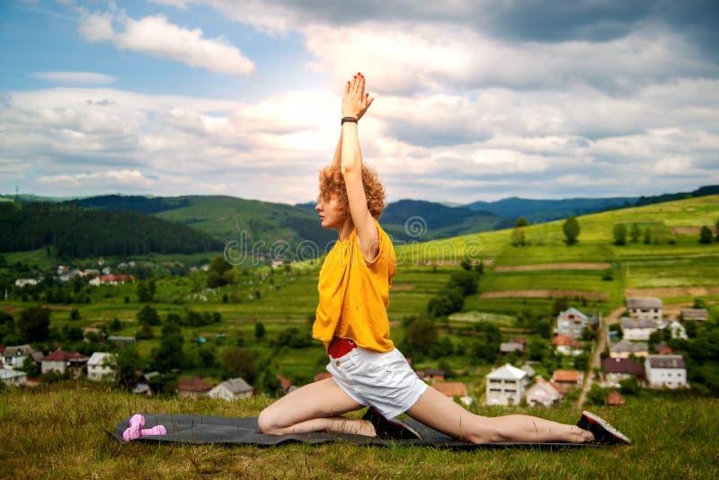 Ung härlig sportkvinna som kopplar av det fria och dricksvatten efter sport Ung kvinna som gör gymnastik och sträcker i naen royaltyfri bild
