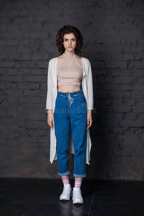 Ung härlig stilfull brunettkvinna, i att stå för tillfällig kläder, att posera på mörk bakgrund för tegelstenvägg och att se kame royaltyfri foto