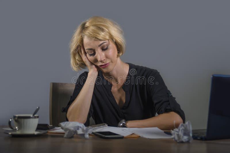 Ung härlig stressad och ledsen blond kvinna som arbetar med tröttat sammanträde för bärbar datordator känsla på kontorsskrivborde arkivfoto