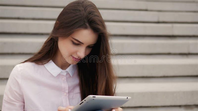 Ung härlig studentflicka som utanför använder en minnestavladator Nätt tonårig kvinnaläsning på luft arkivfoto