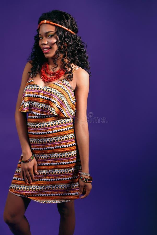 Ung härlig svart kvinna som ler på en lila bakgrund arkivbilder