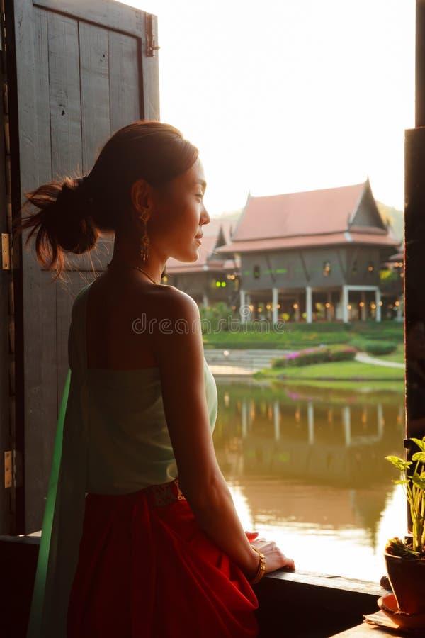 Ung härlig thailändsk asiatisk kvinnadressing i den retro traditionella thailändska dräkten för tappning som ser ut ur fönster Ku fotografering för bildbyråer