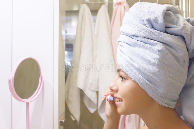 Ung härlig tonårig flicka i en handduk som framme borstar hennes tänder av en spegel arkivfoto