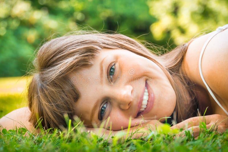 Ung härlig tonårs- flicka som ligger på det gröna gräset arkivbild