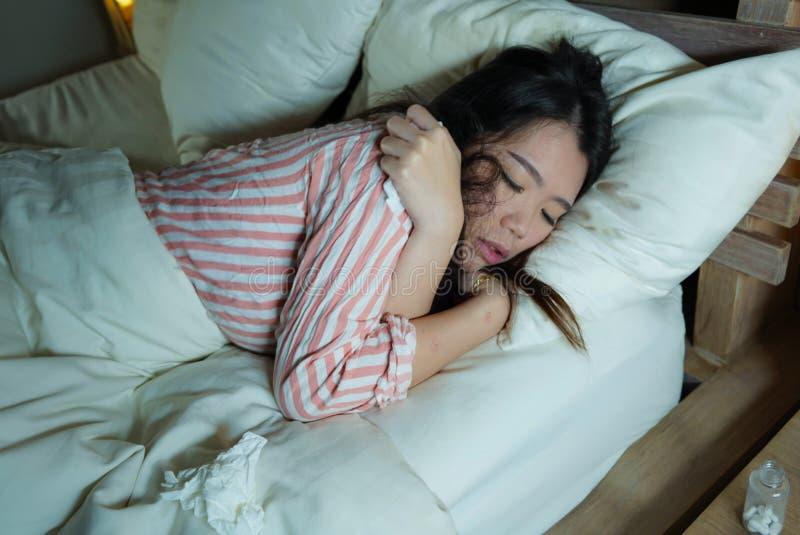 Ung härlig trött och sjuk asiatisk kinesisk kvinna som dåligt ligger på säng i pyjamas på natten med silkespapperlegitimationshan arkivbild