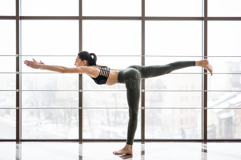 Ung härlig yoga som poserar balansera pinnen Virabhadrasana på en studiobakgrund royaltyfri bild