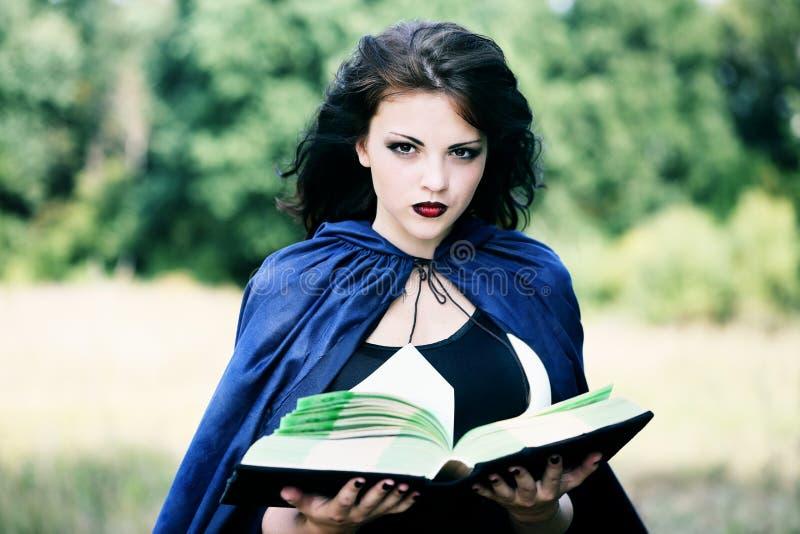 Ung häxa med en bok arkivfoton