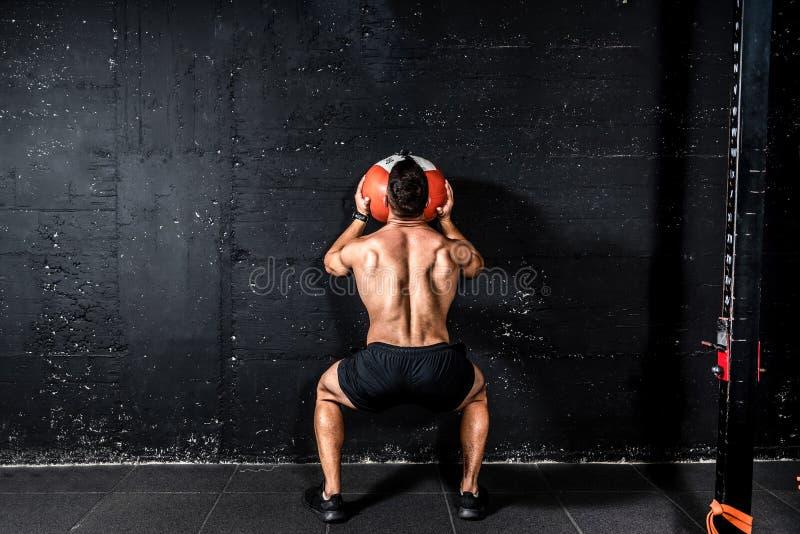Ung, högvårdad, välmående muskelman med stora muskler som kastar upp medicinbollen på väggen för att träna fast kärna royaltyfri foto