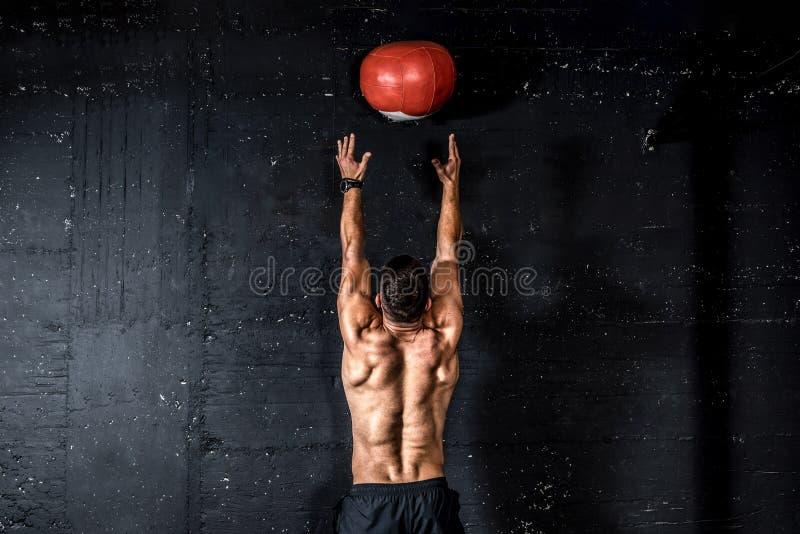 Ung, högvårdad, välmående muskelman med stora muskler som kastar upp medicinbollen på väggen för att träna fast kärna arkivbild