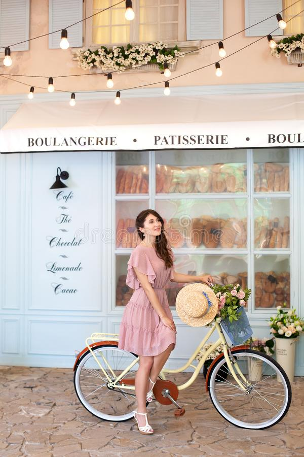 Ung h?rlig, elegantly kl?dd kvinna med cykeln Sk?nhet, mode och livsstil Cykel med korgen av blommor Den befriade flickan arkivbilder