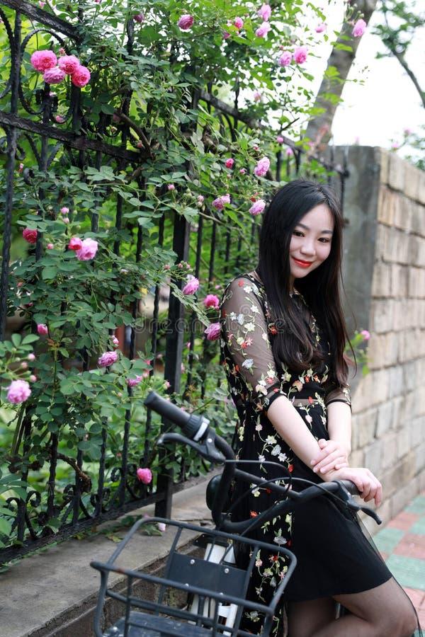 Ung h?rlig, elegantly kl?dd kvinna med cykeln Sunt och att cykla royaltyfria foton