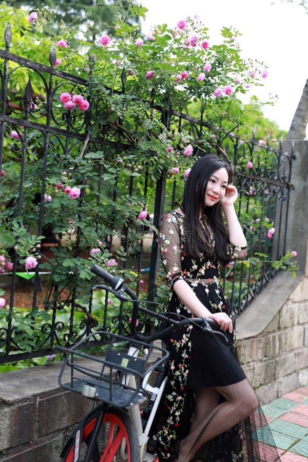 Ung h?rlig, elegantly kl?dd kvinna med cykeln Sunt och att cykla royaltyfri foto