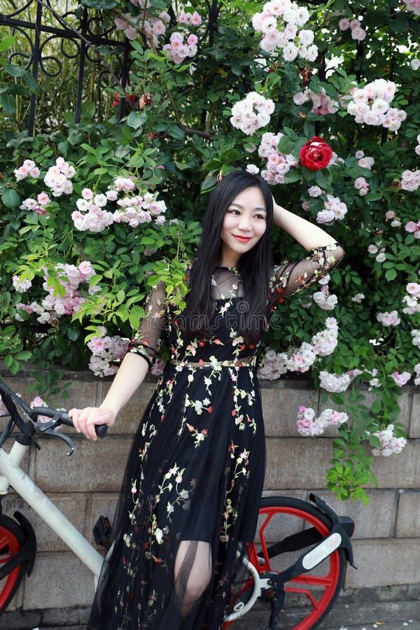 Ung h?rlig, elegantly kl?dd kvinna med cykeln Sunt och att cykla royaltyfria bilder