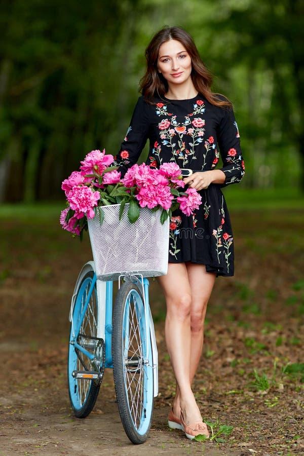 Ung h?rlig, elegantly kl?dd kvinna med den retro cykeln Sunt och att cykla arkivfoton