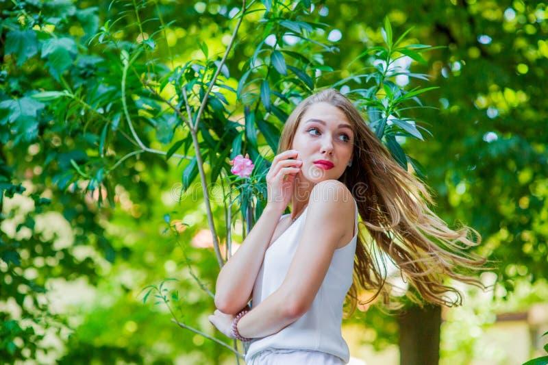 Ung h?rlig flicka som poserar den utomhus- b?rande trendiga vita kl?nningen Sommarstil arkivbilder