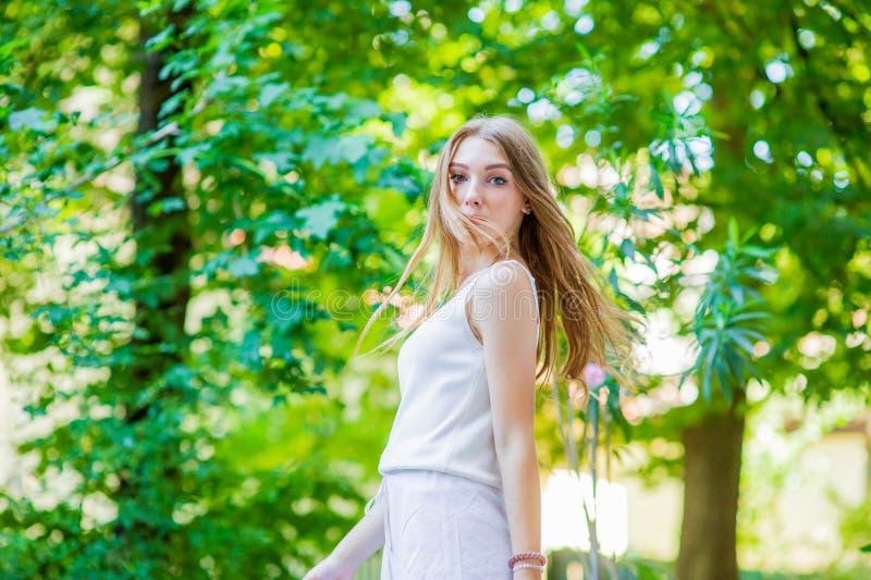 Ung h?rlig flicka som poserar den utomhus- b?rande trendiga vita kl?nningen Sommarstil royaltyfria bilder
