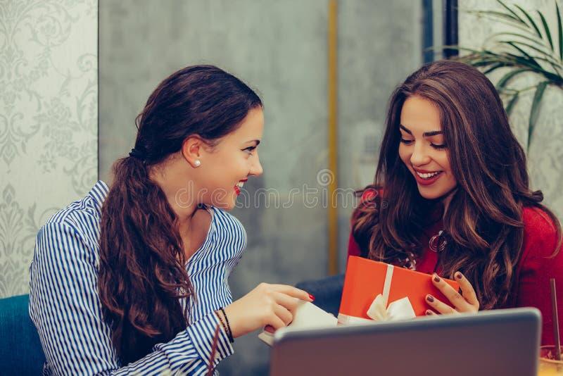 Ung h?rlig flicka som sitter i kaf? med hennes v?n och mottar en g?va arkivbilder