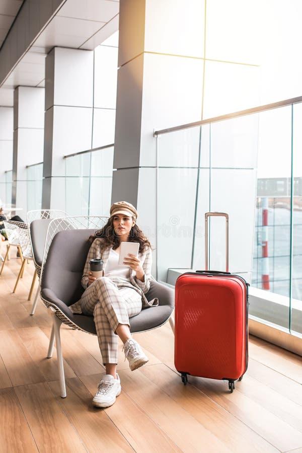 Ung h?rlig kvinna i v?ntande rum f?r flygplats royaltyfri foto