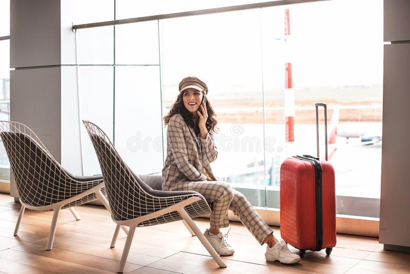 Ung h?rlig kvinna i v?ntande rum f?r flygplats arkivbilder