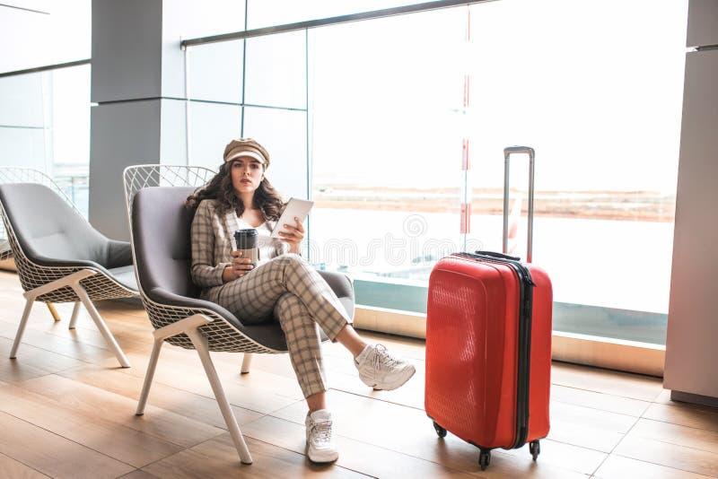 Ung h?rlig kvinna i v?ntande rum f?r flygplats royaltyfri bild