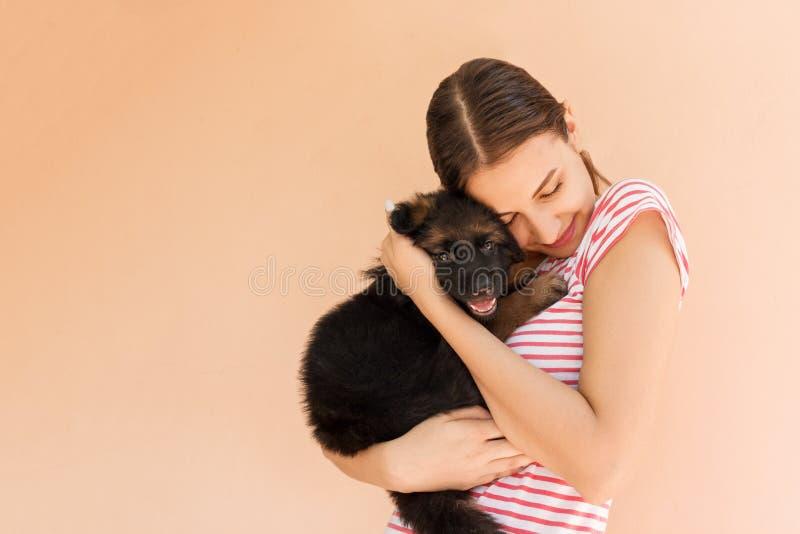 Ung h?rlig kvinna med en svart valp Trevlig kvinna som rymmer och kramar hennes hund royaltyfri fotografi