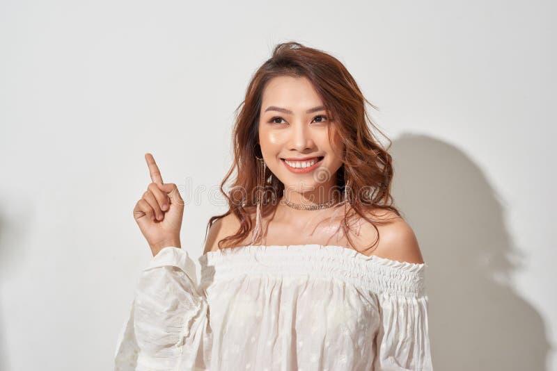 Ung h?rlig kvinna med ett stort leende p? framsida och att peka med handen och fingret till sidan royaltyfria bilder