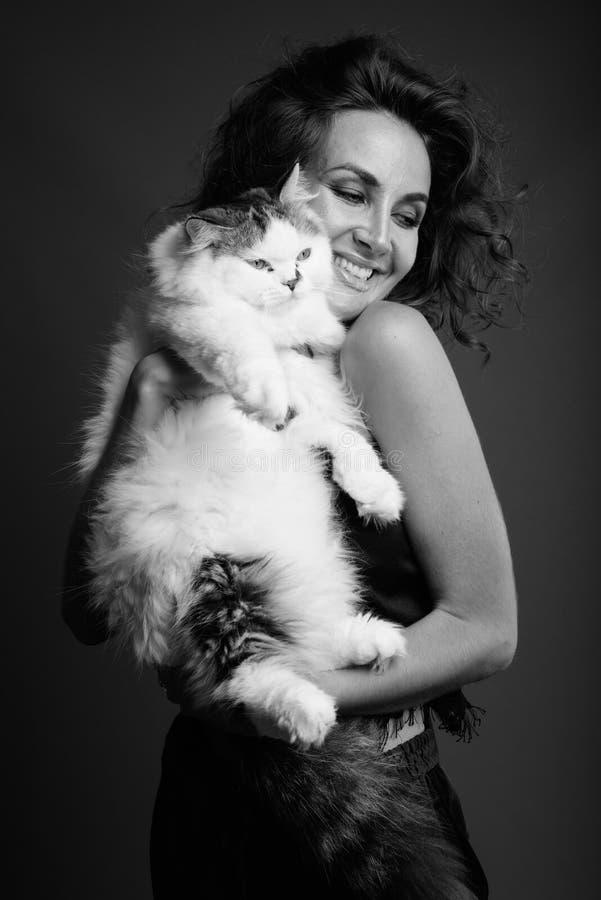 Ung h?rlig kvinna med lockigt h?r som poserar i svartvitt royaltyfria foton