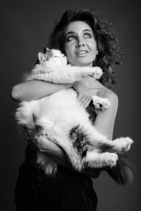 Ung h?rlig kvinna med lockigt h?r som poserar i svartvitt royaltyfria bilder