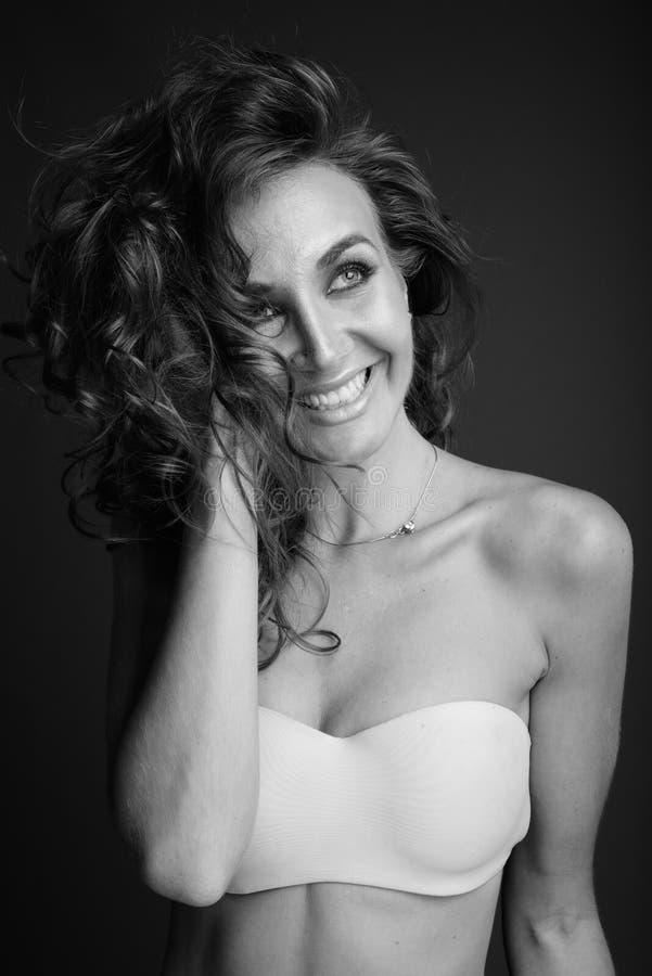 Ung h?rlig kvinna med lockigt h?r som poserar i svartvitt arkivfoton