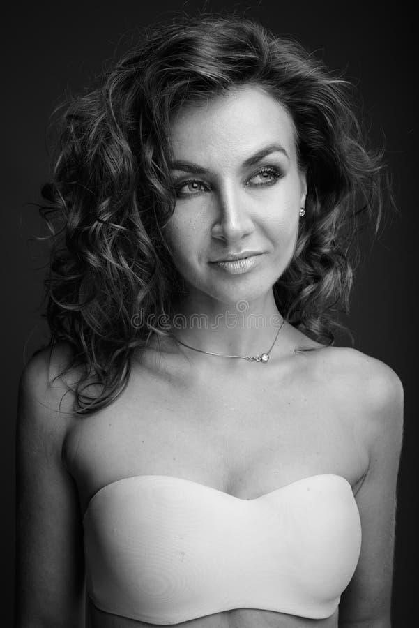 Ung h?rlig kvinna med lockigt h?r som poserar i svartvitt arkivbilder